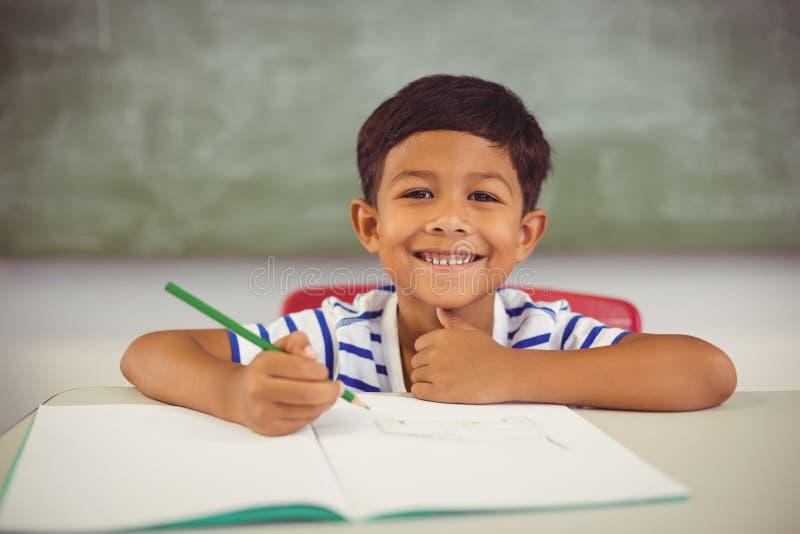 Stående av pojken som gör läxa i klassrum arkivbild
