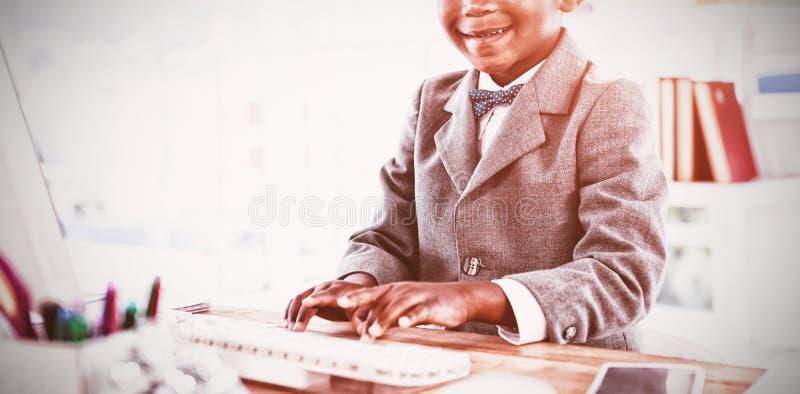 Stående av pojken som imiterar som affärsmannen som använder datoren royaltyfri bild