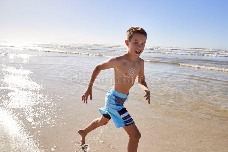 Stående av pojkespring till och med vågor på sommarsemester arkivbild