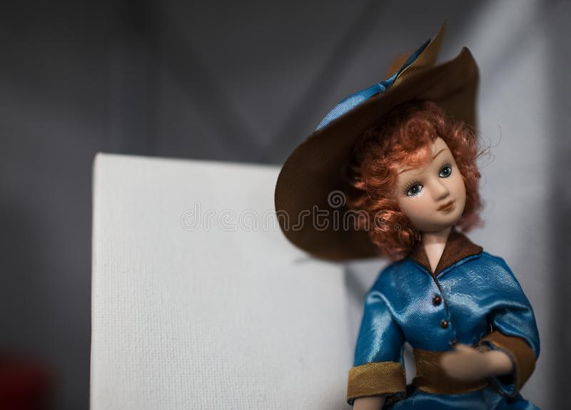 Stående av porslindockan med rött lockigt hår, den bärande blåa klänningen och hatten arkivfoto