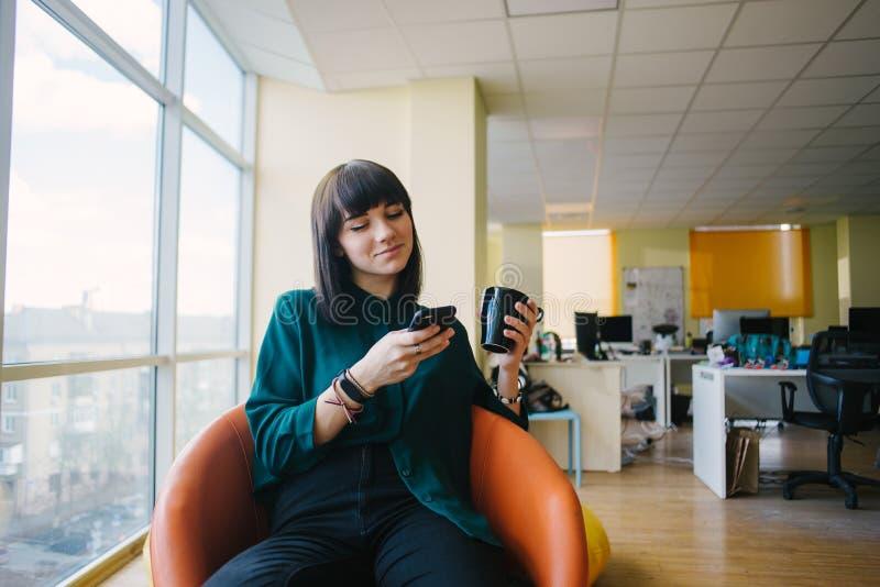 Stående av positivt ungt sammanträde för affärskvinna i det moderna kontoret som ler och ser telefonen fotografering för bildbyråer