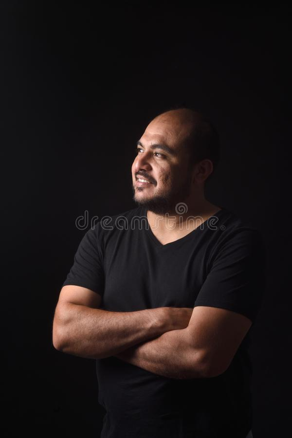 Stående av profilen av ett latinskt - amerikanska manarmar korsade på svart bakgrund som ler royaltyfri foto