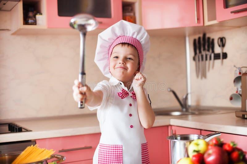 Stående av pysen i hatten av kocken och ett förkläde Liten kockkock i köket Emotionella bilder royaltyfri foto