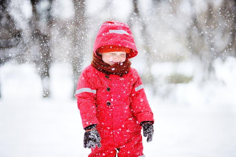 Stående av pysen i röd vinterkläder som har gyckel med snö under snöfall fotografering för bildbyråer