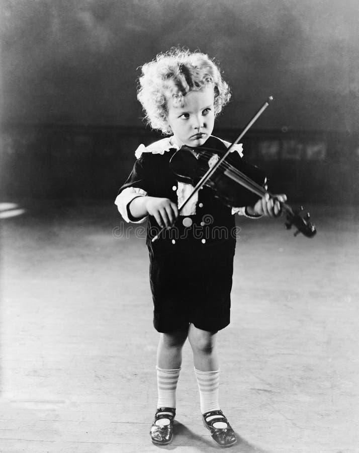 Stående av pysen som spelar fiolen (alla visade personer inte är längre uppehälle, och inget gods finns Leverantörgarantier det royaltyfri fotografi
