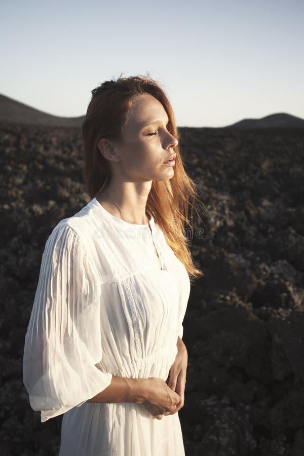 Stående av rödhårig manflickan i den vita klänningen breathink med stängda ögon Lanzarote kanariefågelöar, Spanien royaltyfri foto