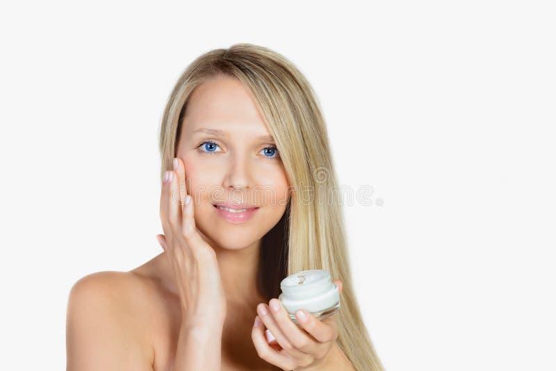 Stående av rörande hud för härlig blond kvinna eller appliceracrea royaltyfria foton