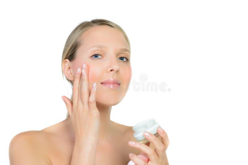 Stående av rörande hud för härlig blond kvinna eller appliceracrea arkivbilder