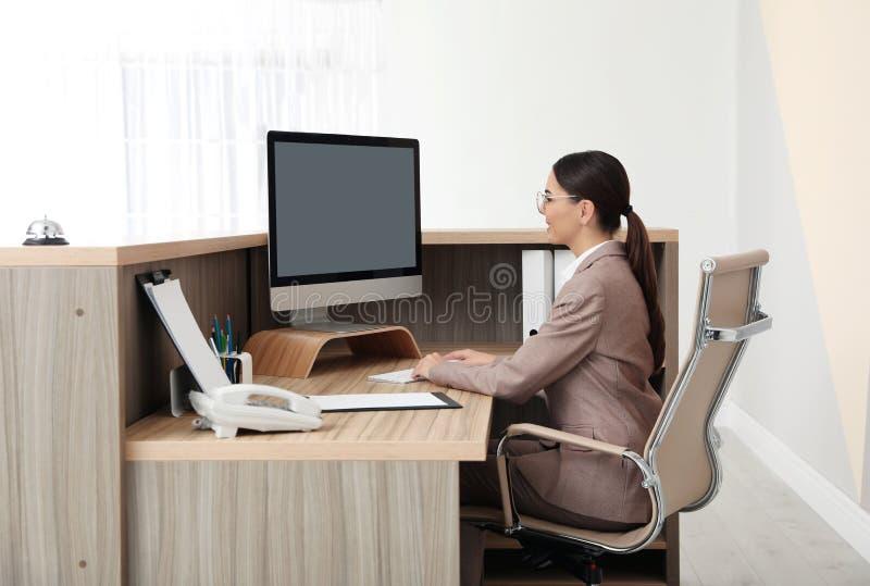 Stående av receptionisten som arbetar på skrivbordet i hotell royaltyfri fotografi