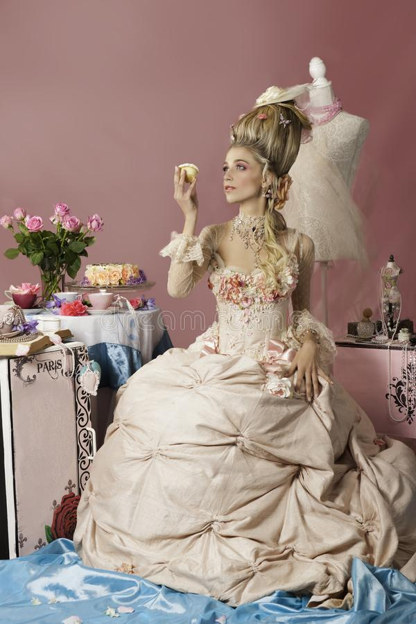 Stående av rokokokvinnan som kläs som den Marie Antoinette innehavkakan arkivbild