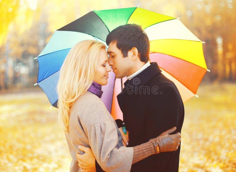 Stående av romantiska kyssande par som är förälskade med det färgrika paraplyet tillsammans på den varma soliga dagen över gula b arkivfoto