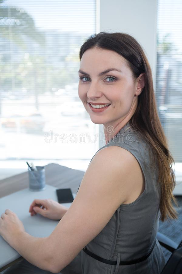 Stående av säkert kvinnligt utövande sammanträde på skrivbordet arkivfoto