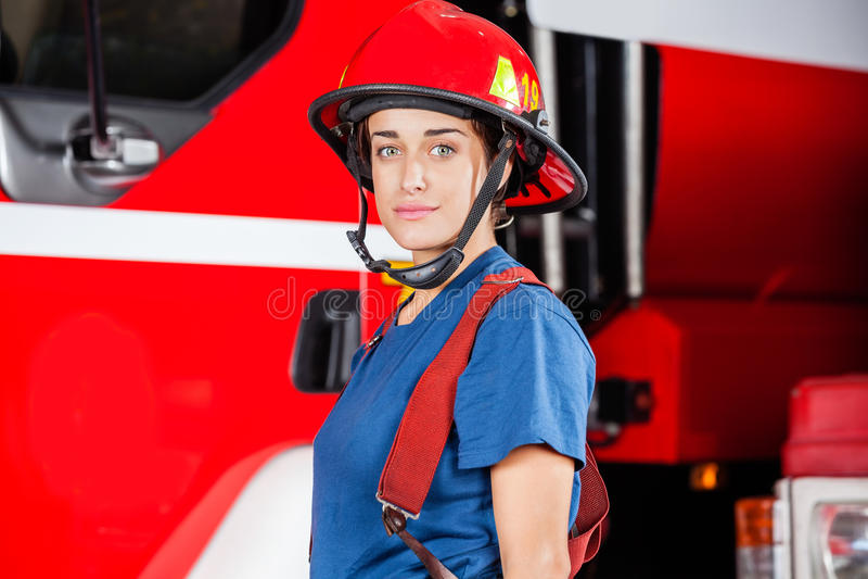 Stående av säkra Firewoman som bär den röda hjälmen royaltyfri foto