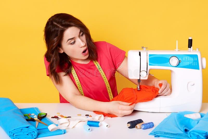 Stående av sömmerskan för ung kvinna som sitter på den vita tabellen och gör plagget i hennes arbetsplats Attraktiv swer syr den  royaltyfria bilder