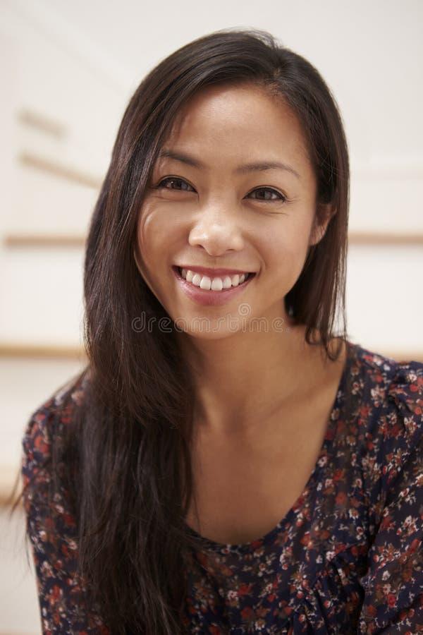 Stående av sammanträde för ung kvinna på trappa hemma royaltyfria foton