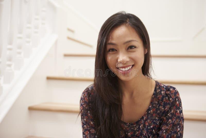 Stående av sammanträde för ung kvinna på trappa hemma royaltyfria bilder
