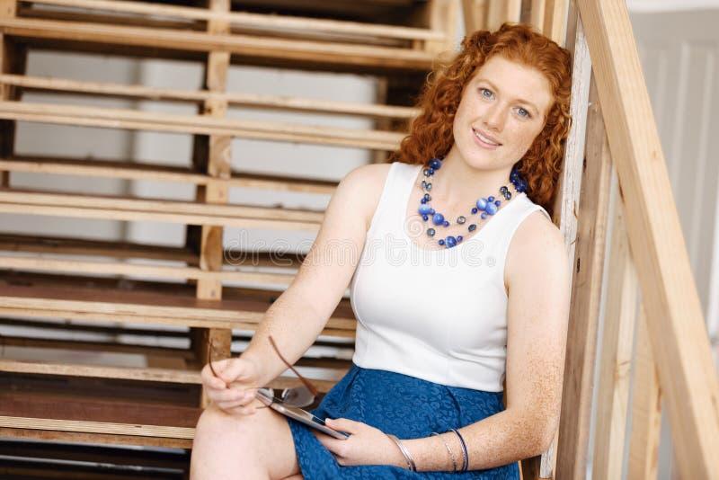 Stående av sammanträde för ung kvinna på trappan i regeringsställning royaltyfria bilder