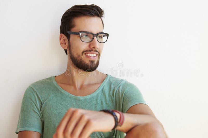 Stående av sammanträde för ung man mot den vita väggen arkivbilder