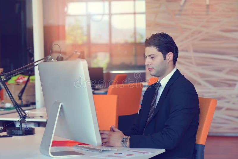 Stående av sammanträde för ung man på hans skrivbord i kontoret fotografering för bildbyråer