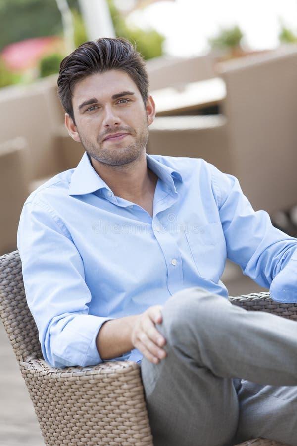 Stående av sammanträde för ung man på stol på det friakafét royaltyfri fotografi