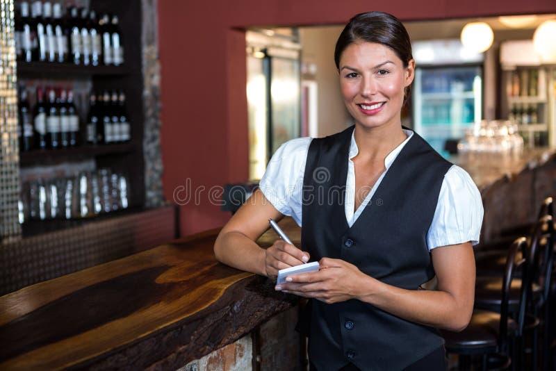 Stående av servitrins som tar beställning i restaurang royaltyfria bilder