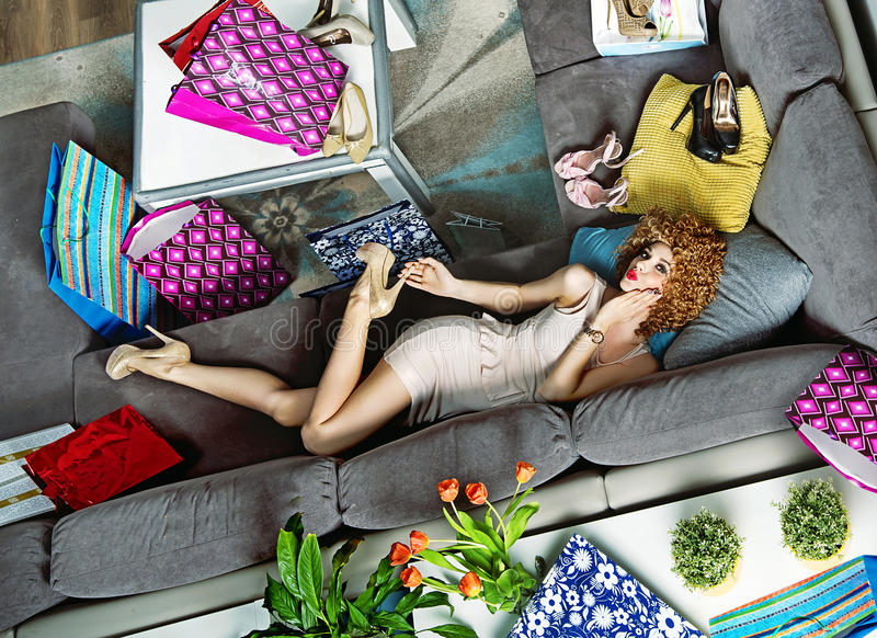 Stående av shopaholic ligga bland många shoppingpåsar arkivbild