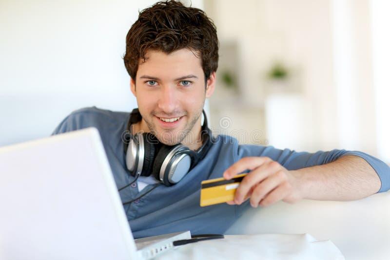 Stående av shopping för ung man på internet med kreditkorten arkivbilder