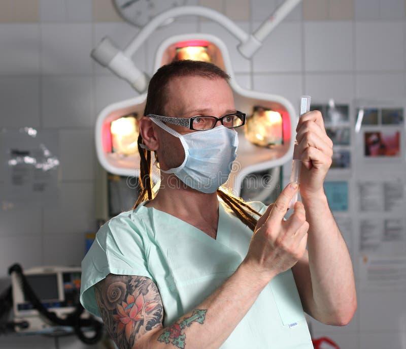 Stående av sjukskötaren ICU med tatueringen och dreadlocks arkivbild