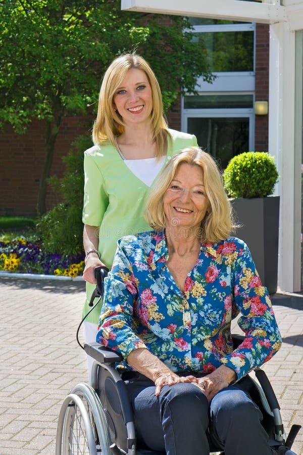 Stående av sjuksköterskan med den höga kvinnan i rullstol arkivbilder