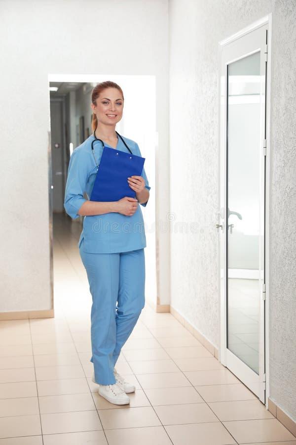 Stående av sjuksköterskan med skrivplattan i sjukhushall arkivbild