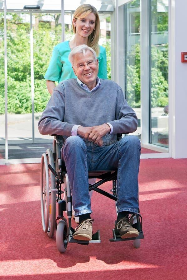 Stående av sjuksköterskan Pushing Senior Man i rullstol royaltyfri foto