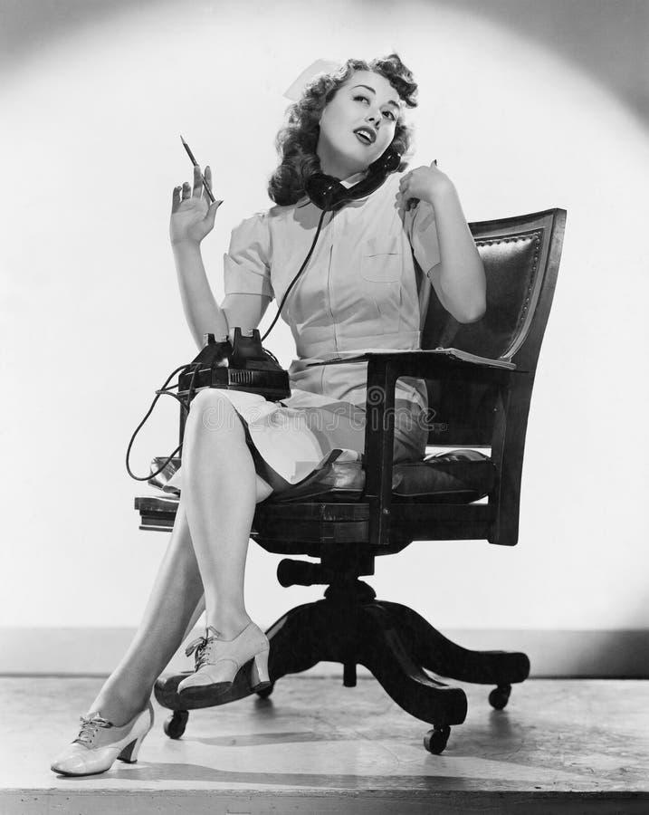 Stående av sjuksköterskan som talar på telefonen (alla visade personer inte är längre uppehälle, och inget gods finns Leverantörg arkivbild