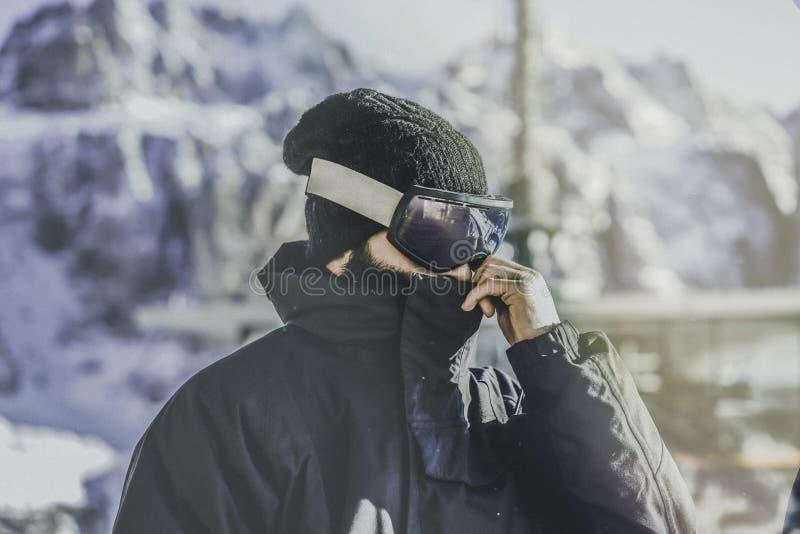 Stående av skäggigt barn snowboarded i sunglassmaskering, på skidasemesterorten på bakgrunden av berg och blå himmel arkivbilder