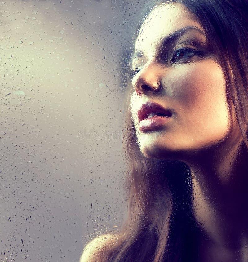 Stående av skönhetflickan bak det våta exponeringsglaset arkivfoto