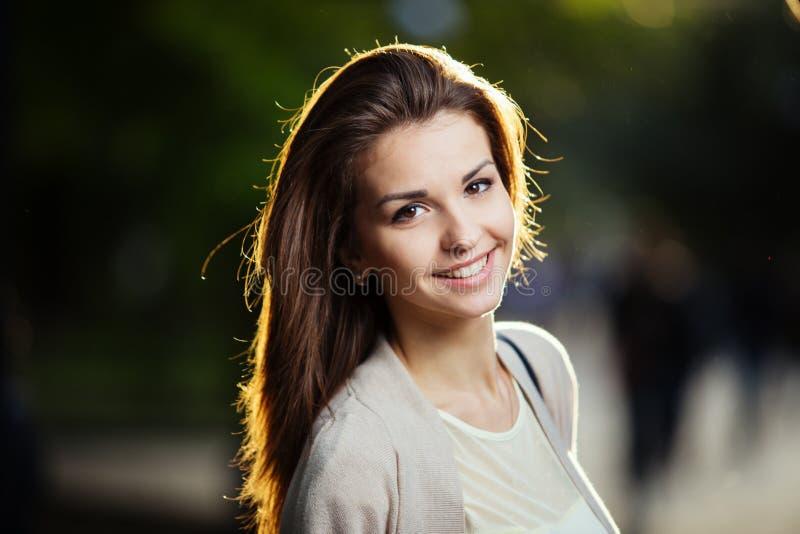 Stående av skönhetkvinnan med perfekt leende som går på gatan och ser kameran, solnedgångljus royaltyfria bilder