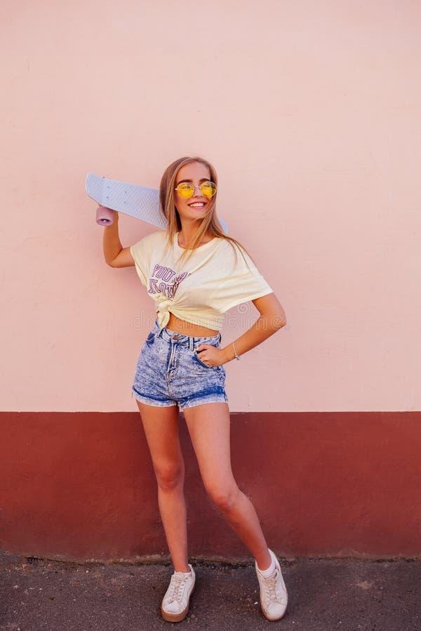 Stående av skönhetmode som ler unga kvinnor med gul solglasögon som rymmer longboard Flyghår utomhus- fotografering för bildbyråer