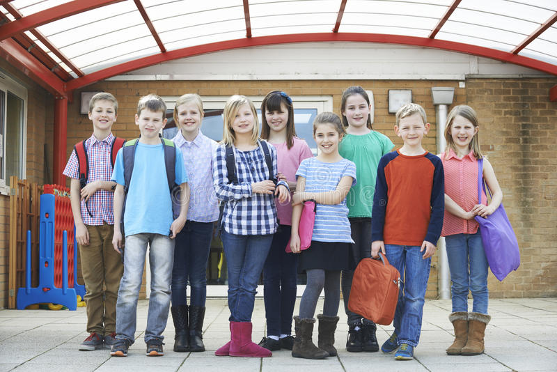 Stående av skolaelever utanför bärande påsar för klassrum fotografering för bildbyråer