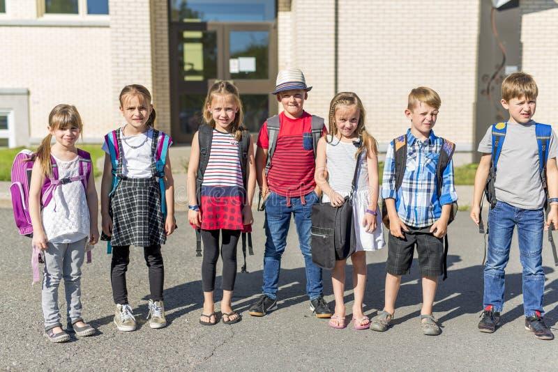 Stående av skolaelever utanför bärande påsar för klassrum royaltyfri foto