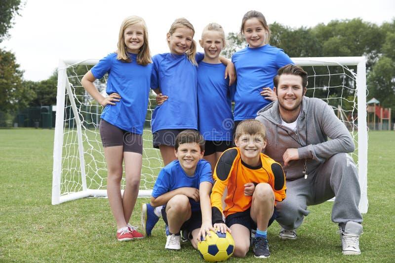 Stående av skolafotboll Team With Coach royaltyfri foto