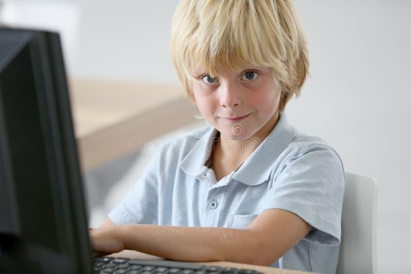 Stående av skolapojken på den skrivbords- datoren royaltyfri fotografi