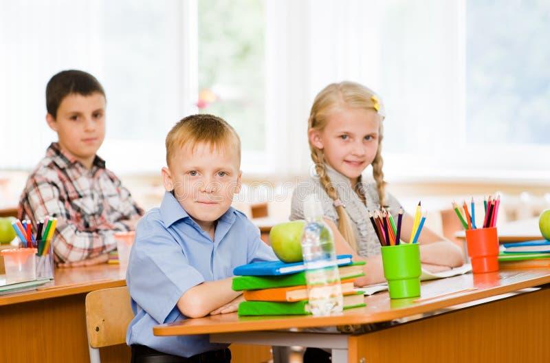 Stående av skolbarn som ser kameran på arbetsplatsen royaltyfri fotografi