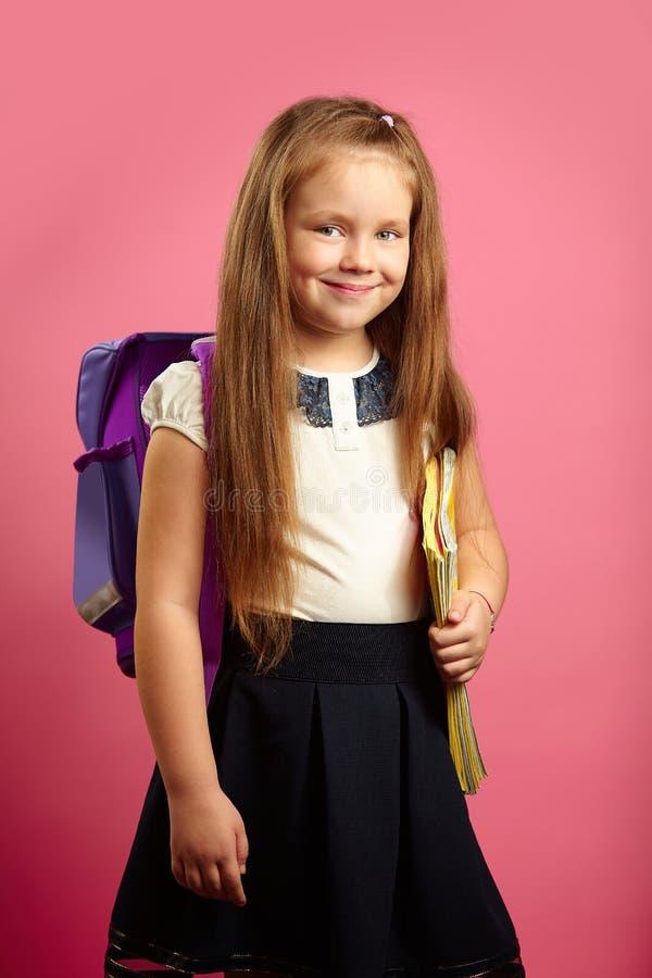 Stående av skolflickan med ryggsäcken och anteckningsböcker som går till första klass, över isolerad rosa bakgrund barnet går öve arkivfoto