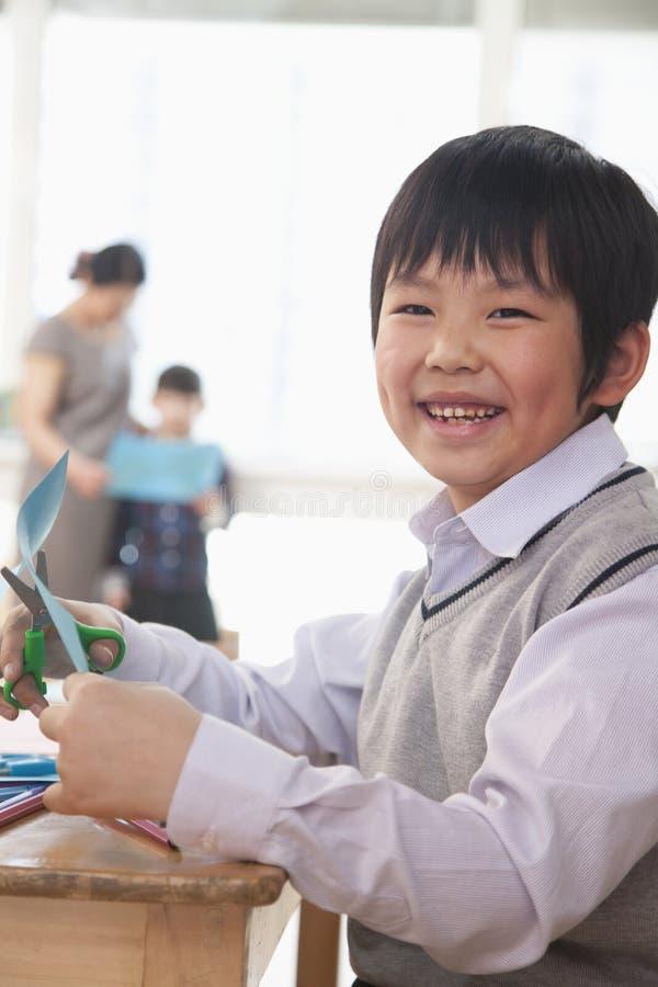 Stående av skolpojken som gör konsthantverk, Peking arkivbild