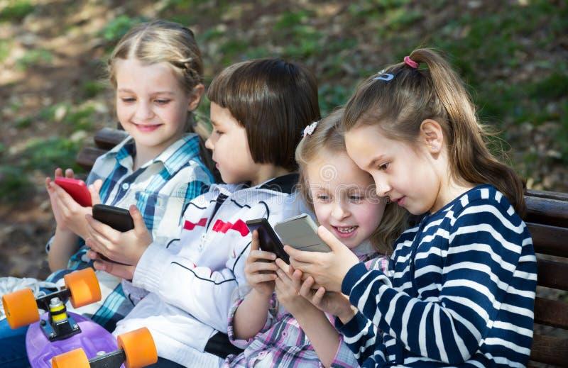 Stående av små ungar som spelar med telefoner fotografering för bildbyråer