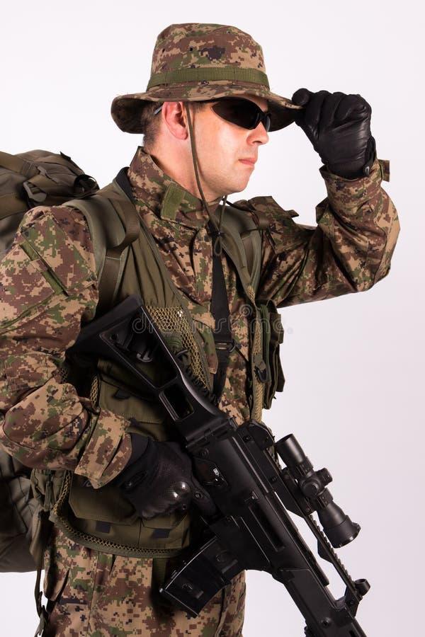 Stående av soldaten med hatten och vapnet på vit bakgrund - nära övre arkivbild