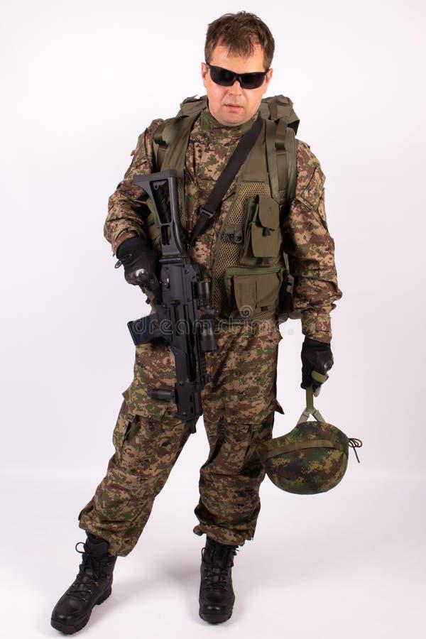 Stående av soldaten med hjälmen och vapnet på vit bakgrund royaltyfri foto