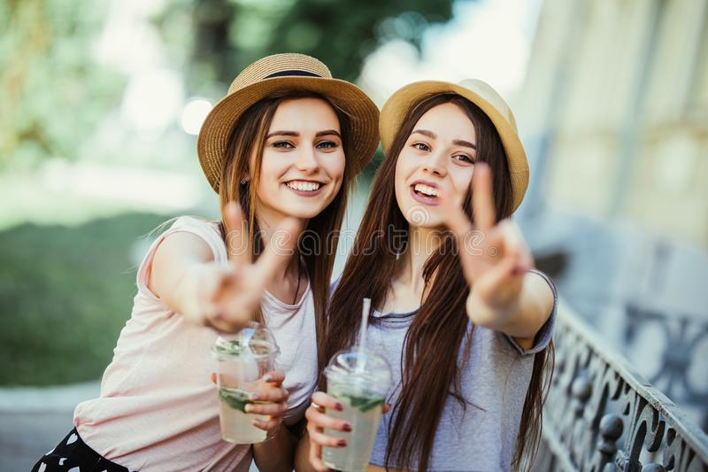 Stående av sommar som två ler unga flickor som vinkar fred till kameran, medan stå det friasamtal- och drinkcoctailar fotografering för bildbyråer