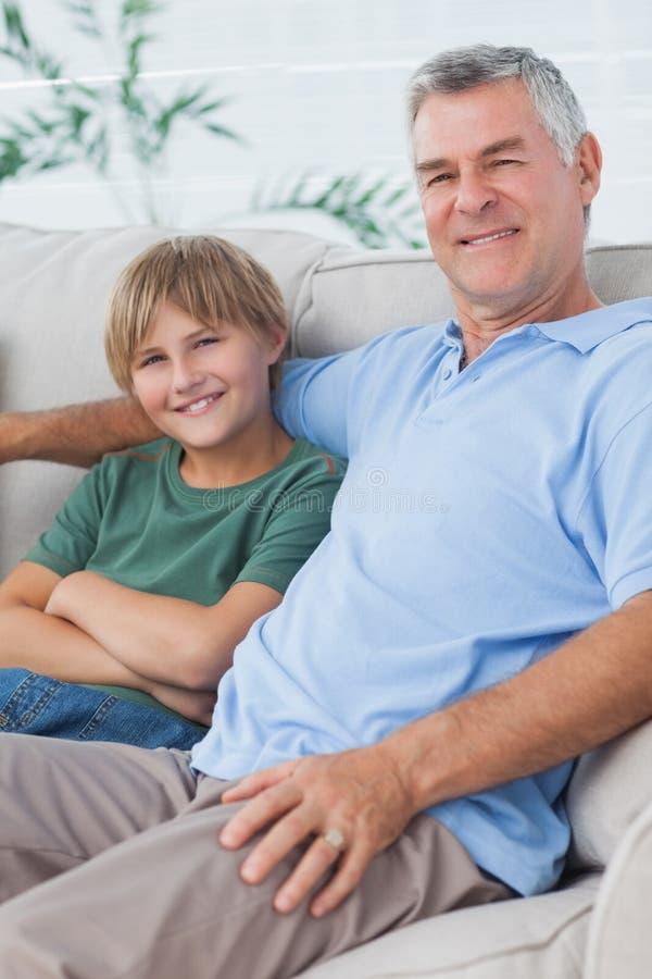 Stående av sonson- och farfarsammanträde på soffan arkivbilder