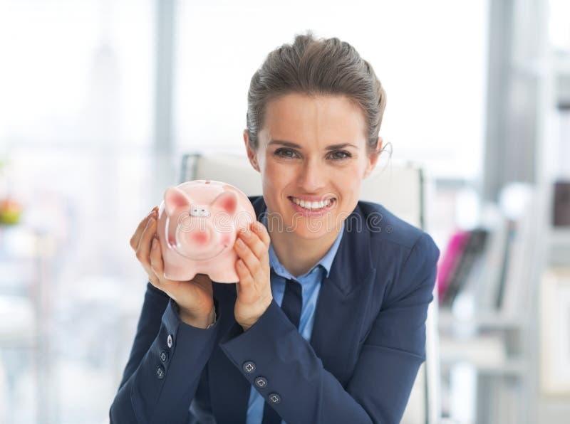Stående av spargrisen för visning för affärskvinna arkivfoton