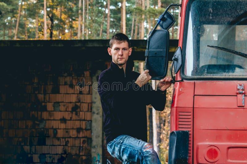 Stående av ställningen för ung man på sida på lastbilkabinen royaltyfri foto
